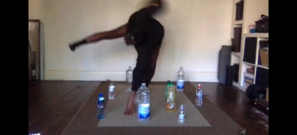 A screen shot. Kyra dancing in a living room, balancing on one hand and one leg. The hand is placed amongst some plastic bottles standing on the floor. A straight leg to her right balances her.