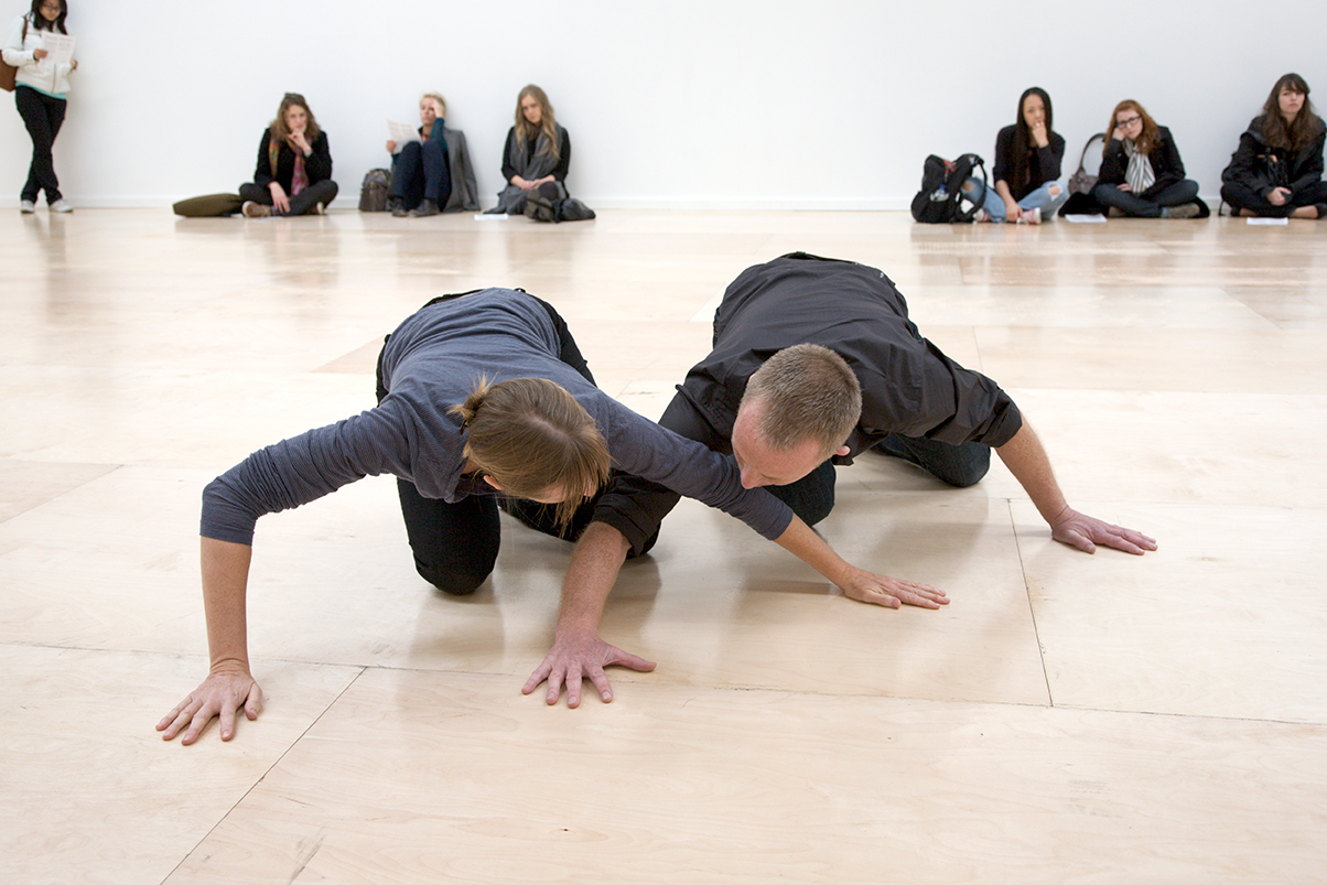 Two dancers on all fours, on the floor. Their bent arms are spread and overlap each other.