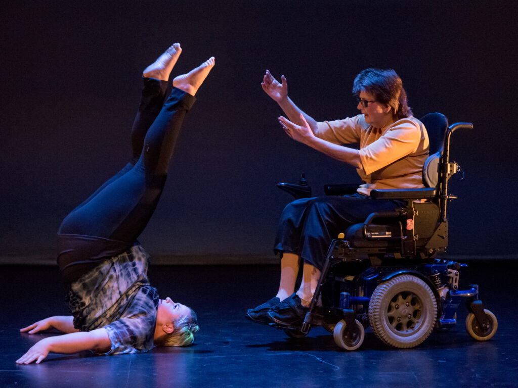 Kaylee Borgstrom and Iris Dykes in Help! Kaylee, a white woman with green hair is suspended on her shoulders, her feet in the air. Iris, an older white woman using a power wheelchair, reaches her hands out for Kaylee's feet.