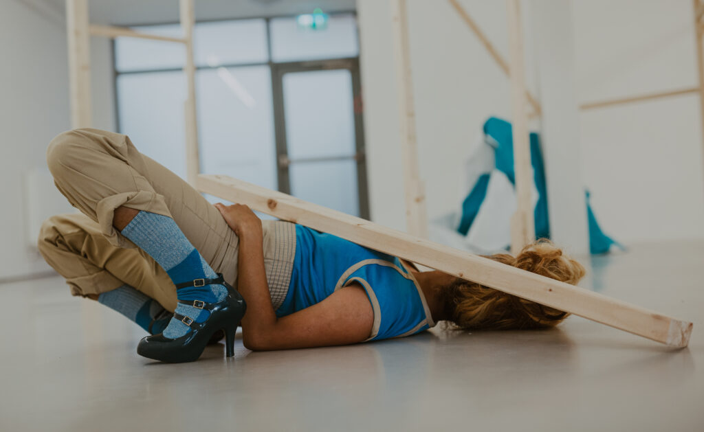 Project: The Drawing Machine Experiment: Side view of a body laying on the floor, on their back holding a plank of would. They are wearing a blue and cream jumpsuit, blue socks socks and dark blue triple strap heels.