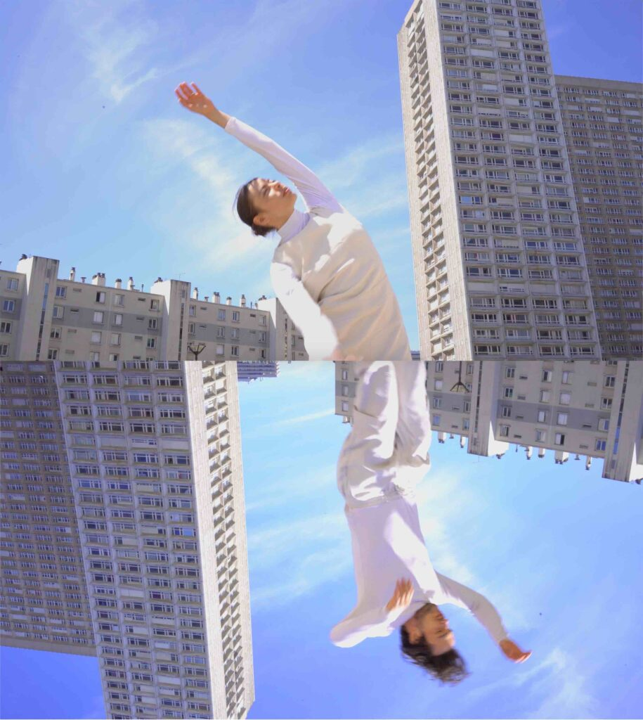 A split image of two people with their arms in the air. The background behind them is of tower blocks and blue clear sky. The bottom image is upside down.