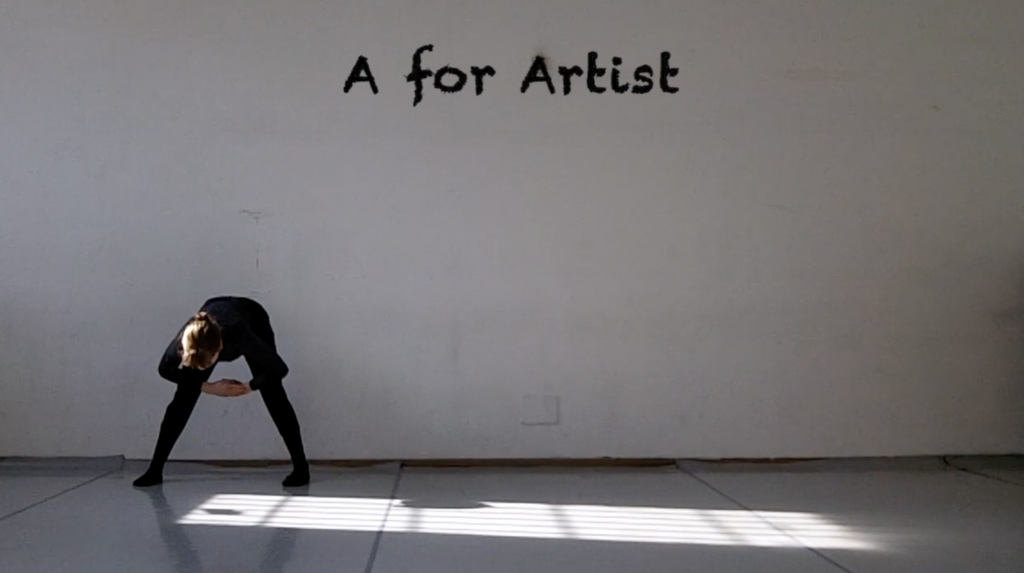 Person in a studio bent over making the shape of a capital A. Above them on the wall is 'A for Artist' written in black paint.
